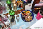 Behind the makeup mirror. The little bowl has mini bottles and rollerballs.